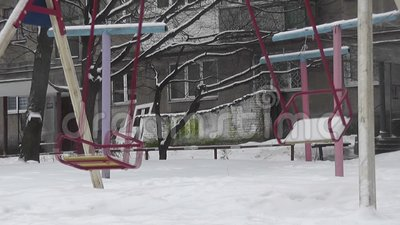 Empty swing in winter yard. Urban scene building background stock video