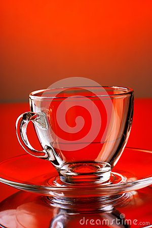 Empty transparent glass mug on red background