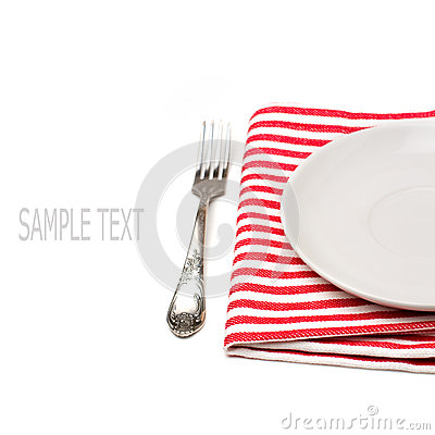 Empty white plate on tablecloth with fork