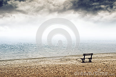 Empty wooden bench on the beach in cloudy weather