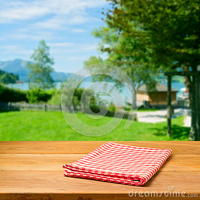 Empty wooden table with checked tablecloth over beautiful landscape.