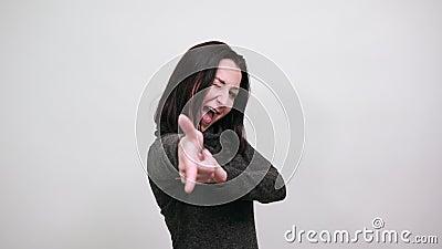 En attraktiv kaukasisk ung kvinna som pekar finger åt kameran, vindar, ser glad ut arkivfilmer