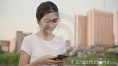 En cámara lenta - Alegre blogger asiática de turismo usando un smartphone para su dirección y buscando el mapa de ubicación mi metrajes