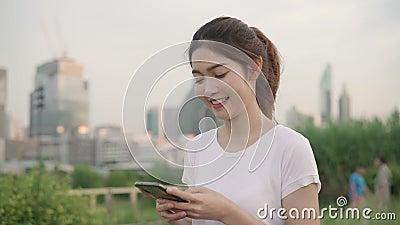 En cámara lenta - Alegre blogger asiática de turismo usando un smartphone para su dirección y buscando el mapa de ubicación mi almacen de metraje de vídeo