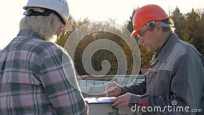 En el tejado los trabajadores de construcción en casco discuten la construcción según plan almacen de video