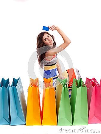 En flicka i en lång klänningfärg med shopping bags