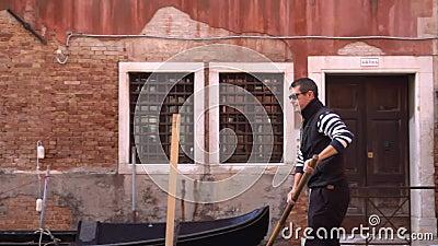 En Gondolier paddlar genom storkanalen i Venedig arkivfilmer
