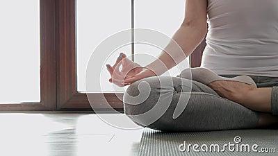 En gros plan, une femme est assise sur le sol en position de lotus. Exercices à domicile dans le yoga banque de vidéos