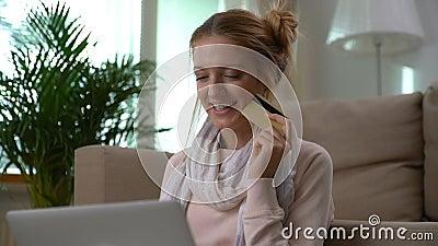 En härlig ung kvinna använder online-sammanträde för guld- kreditkort på golvet Dockaskott arkivfilmer