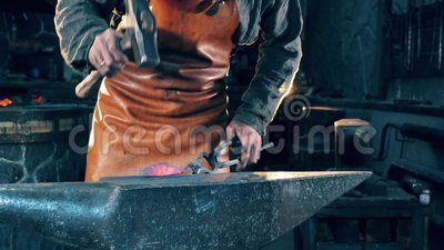 En hovslagare använder en hammare för att forma en kniv på en smedja lager videofilmer