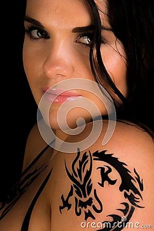 Unga sexiga kvinnor med en tatuering på henne knuffar