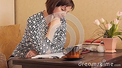 En kvinna skriver handskriven text med en kulspetspenna i en anteckningsbok arkivfilmer