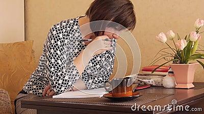 En kvinna skriver handskriven text med en kulspetspenna i en anteckningsbok stock video