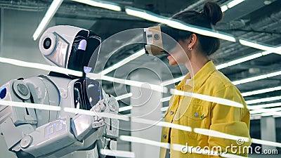 En kvinna trycker på robotens hand, medan bära VR-exponeringsglas lager videofilmer