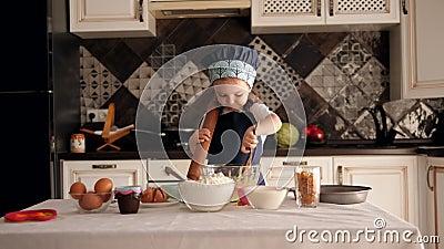 En liten flicka i en hatt och en apron äter råkakedeg med en träsked arkivfilmer