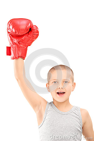 En lycklig unge med röda boxninghandskar som gör en gest triumf