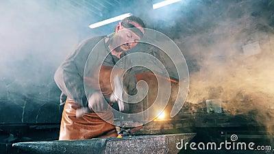 En man arbetar på en smedja som slår en kniv med en hammare lager videofilmer