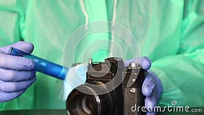 En man i gummihandskar, en regnrock och glasögon avlägsnar damm från en kamera med en borste Rengöring av fotografisk utrustning  arkivfilmer