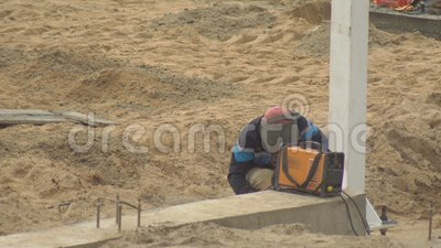 En man som använder en svetsmaskin svetsar metallytor på en byggarbetsplats, kopieringsutrymme, industri stock video