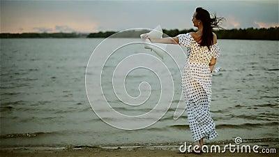 En mellersta åldrig kvinna i ett långt sommarklänninganseende på stranden som sätter av hennes hatt och tycker om vinden lager videofilmer