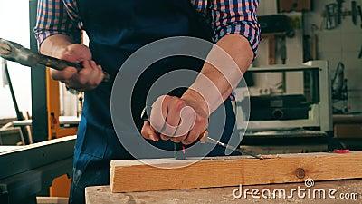 En snickare använder en hammare och en stämjärn för att bearbeta trä stock video