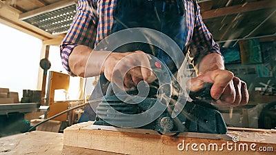 En snickare karvar träpinnen med ett instrument arkivfilmer