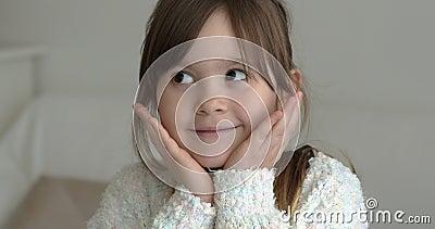 En sorglig liten flicka som tittar på kameran med hans på sina kinder le lager videofilmer
