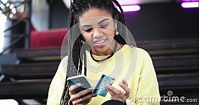 En un orden étnico africano constructivo moderno de la señora de la oficina algo en línea usando su smartphone en el extremo ella almacen de video