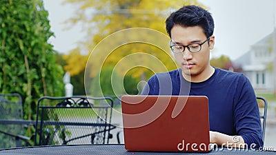 En ung asiatisk man arbetar med en bärbar dator Sammanträde utomhus i en typisk amerikansk stad arkivfilmer