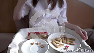 En ung kvinna har en romantisk frukost på morgonen. Kaffe och ordkärlek från cookies Överraska på Alla hjärtans dag lager videofilmer