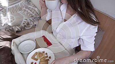 En ung kvinna har en romantisk frukost på morgonen. Kaffe och ordkärlek från cookies Överraska på Alla hjärtans dag arkivfilmer