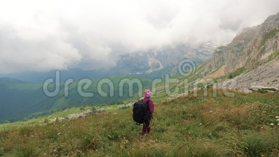 En ung kvinna med ryggsäck är på väg in i vackra kaukasiska berg Lady går mot toppmötet lager videofilmer
