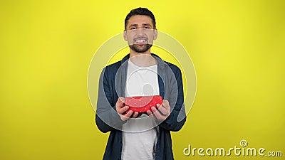 En ung man i en vit T-shirt fångar en låda med en gåva i handen, tittar på kameran och ler, gul bakgrund stock video