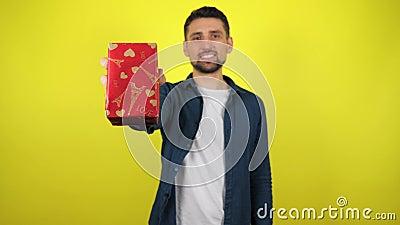 En ung man i en vit T-shirt har en gåva i handen och leenden i kameran, gul bakgrund stock video