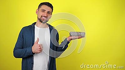 En ung man i en vit T-shirt har en gåva i sin handflata, leenden och föreställningar som gul bakgrund lager videofilmer