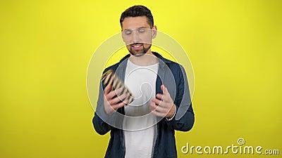 En ung man i en vit T-shirt kastar en låda med en gåva från hand till hand och en gul bakgrund arkivfilmer