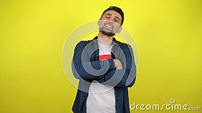 En ung man i en vit T-shirt kramar en låda med en gåva, tittar på kameran och ler, gul bakgrund lager videofilmer