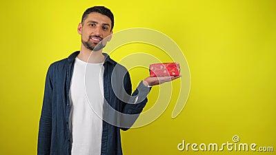 En ung man i en vit T-shirt-show med en gåva i handen och ett leende, gul bakgrund lager videofilmer