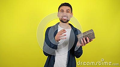 En ung man i en vit T-tröja kastar en låda med en gåva från hand till hand, tittar på kameran och ler arkivfilmer