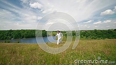 En ung man kör längs en grön kulle framme av en sjö lager videofilmer