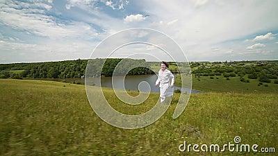 En ung man kör längs en grön kulle framme av en sjö arkivfilmer