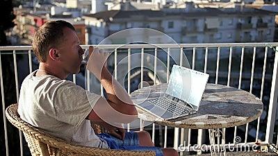 En ung man på balkongen dricker en drink och jobbar på sin bärbara dator lager videofilmer