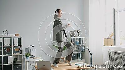 En vacker kontorsarbetare i kostym som dansar på skrivbordet med hörlurar