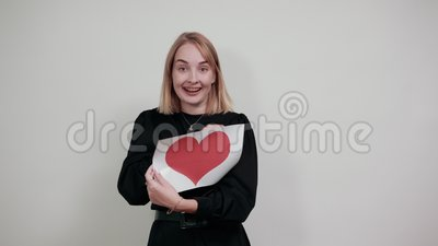 En vacker kvinna som håller rött hjärta med kopieringsutrymme isolerat på grå väggen arkivfilmer