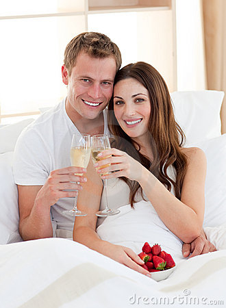 Enamored couple drinking champagne lying in bed