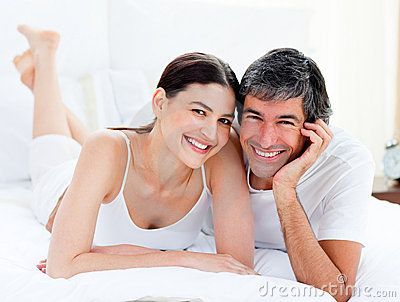 Enamored couple embracing lying on their bed