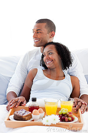 Enamored couple having breakfast on their bed