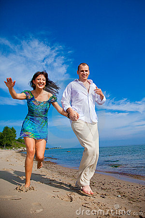 Enamored couple running along the coast of sea