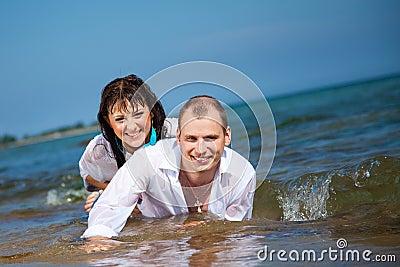 Enamored man and girl lying in waves of sea