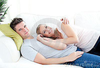 Enamored young couple lyingo together on the sofa